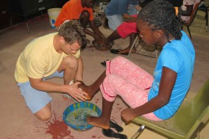 John Helms washes camper's feet at final worship service.
